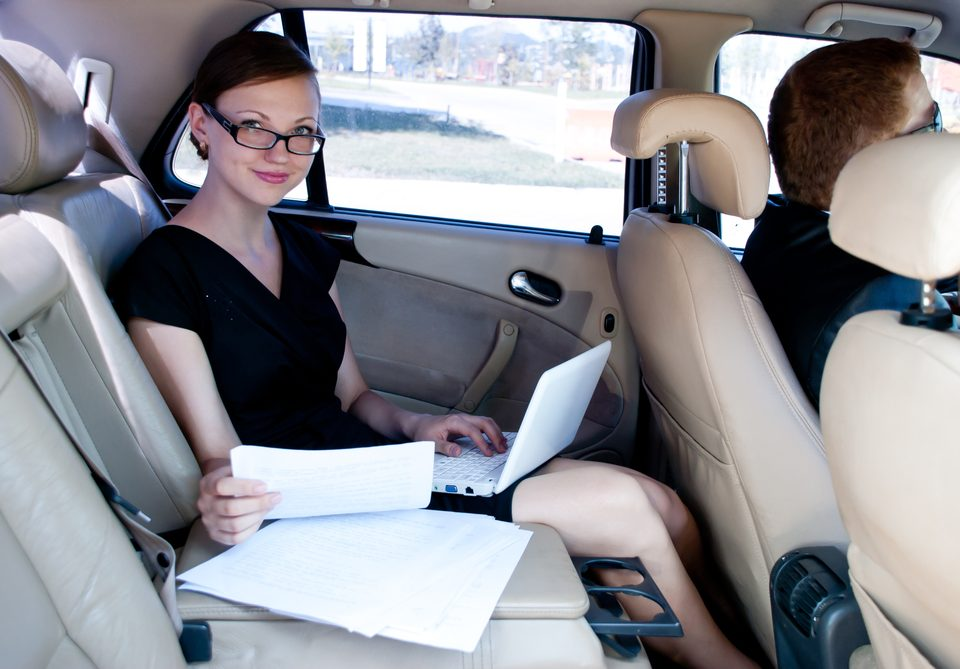 business travel - busy businesswoman with document and laptop in car