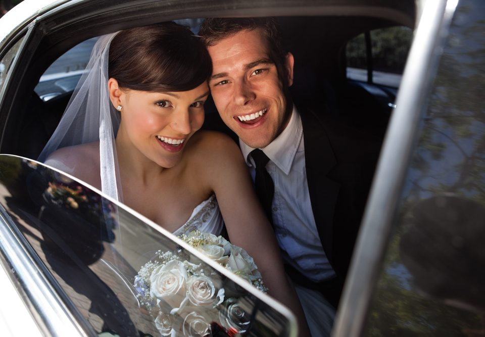 A Newlywed Couple Being Chauffeured in a Limo